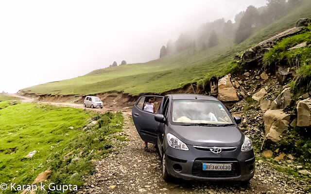 Hello everyone. I may not be good with words but somehow I am going to share about one of the most exciting and memorable trip I had with my family during monsoons of 2012The destination was Prashar lake, situated at a height of 2730 meters above sea level, 49 km north of Mandi, a buzzling town situated in Himachal Pradesh. It's a place about which very few people know, but once anyone visits Prashar, he longs to come back againFor convenience of visiting tourists, recently HPPWD and HP Forest Department constructed different rest houses. In addition a Trekker's Lodge was also constructed which is more sophisticated than othersThe bookings can be done from respective offices in MandiAfter making all the necessary arrangements including food etc. , we a group of 15 family members started from Mandi at about 4 pm. It was a risk though in monsoons because almost 25 km of road was a muddy tarmac and had become slippery, thanks to some contractor who didn't do a good jobAs we came closer to our destination, more the chill in air increased. This was my second visit to Prashar. Earlier I had trekked almost 14 kms to reach there way back in year 2000. The route chosen was via Katindi, Kataula and last thickly populated place en route is Baghi, which is 28 kms from Mandi approximately. Till here the road condition is good. After crossing Baghi you will find lesser number of inhabitants. As you move higher, just 5 km before Prashar you will find one room mud & stone houses, inhabited by shepherds or gaddi's as they are locally knownWe reached Prashar at 7 pm as last 14 kms of distance had to be covered in fog. The temperature was a whooping 2 degrees celcius in evening. After some tea everyone settled down in quilts and blankets, as that was no doubt the need of hour. With fog and darkness all around there was nothing to be explored nearby, so after a tasteful dinner I sleptI woke at around 6 am in morning. The scenery outside was mesmerizing. It had rained during night. The clouds were making way for mountains to be seen. The cold didn't stop me from getting my camera and go for a short exploration spree around. The surroundings were full of many types of flowers. The area had various types of flora.At around 8 am it started raining again, and that is when I noticed one of our cars had a flat tyre. It was replaced then and there as chances of heavy rainfall were expected in later part of the day. At such places there are no workshops etc. so one has to come well prepared beforehandOnce all were ready luckily it stopped raining. We all started for the famous Prashar Rishi Temple and Lake. It's a 15 minute walk from the rest house when you reach and gaze down to see a lake having crystal clear water and a temple premises consisting of three pagoda architecture buildingsThe myth about Prashar Lake is that it was formed after Saint Rishi performed meditation hereThe depth of the lake is still uncertain. Rumors are that the main temple is beneath the lake.  It is also said that there is a big treasure beneath the lake, but no one dares to go and find out. Once some foreign national took a dip in lake to reach the depth.  It is said that once he returned he lost his visionBeing a Sunday the secluded place was abuzz with activity with many tourists thronging to seek blessing and enjoy their SundayOne can make out that how much worshipped diety is Prashar Rishi as large number of followers were seen seeking blessingsThere are two shops which serve delicious rajmah-rice and tea in vicinity of lakeAs the day was foggy, the beauty of Lake was at its bestOne must surely visit the place.
