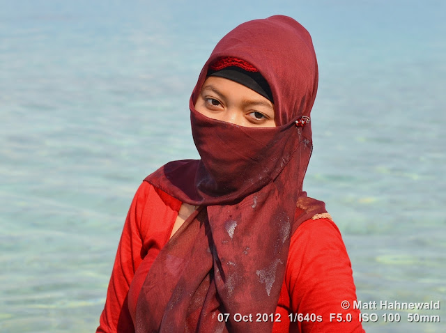 street portrait, Indonesia, Central Sulawesi, young Indonesian Muslim lady, maroon niqab, beach, beautiful eyes, smiling eyes, charming, outgoing, smiling, posing