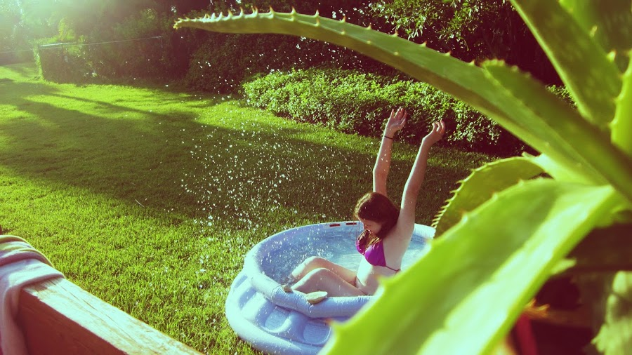 Little Girl in Hot Pink Bikini Playing in Blue Kiddie Pool With Aloe Vera Plant Looking On