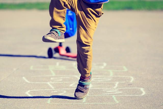 Menino brincando de pular amarelinha