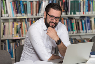 Photo of a young man with a laptop in a library