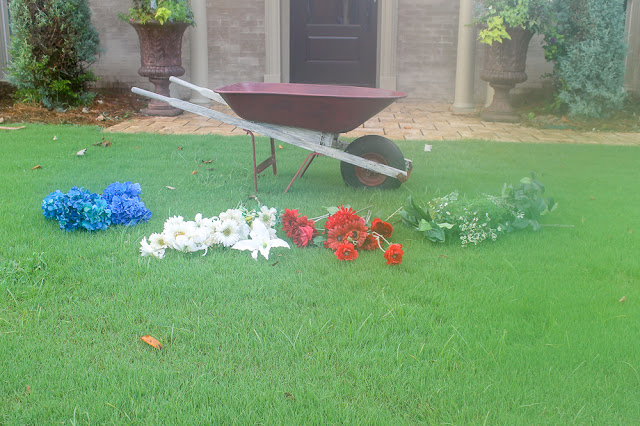 arrange flowers in old wheelbarrow