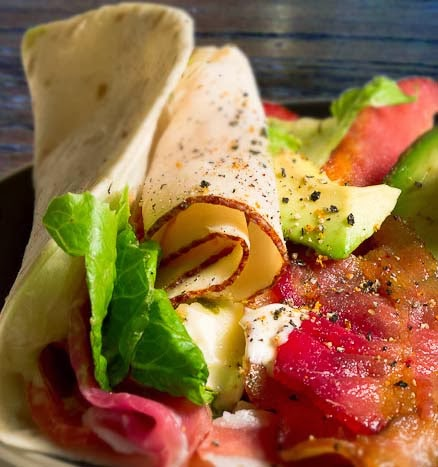 Chicken Wrap with Sliced Chicken Breast, Bacon, Tomato, Avocado, and More.