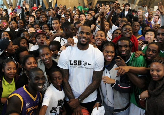 image of LeBron James surrounded by kids, mostly Black kids, who he helps through his foundation