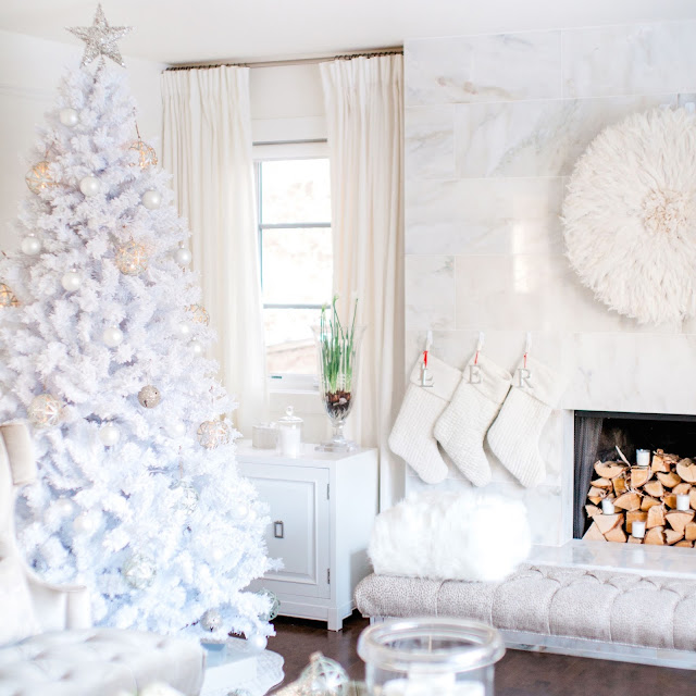 Fluffy white flocked Christmas tree next to a marble fireplace with white velvet pottery barn stockings