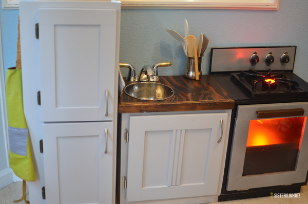This little play kitchen was made from old cabinets and includes electricity for a fake oven and stovetop!
