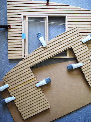 Walls of a dolls' house kit, with weatherboarding clamped to them and a plain wall underneath them.