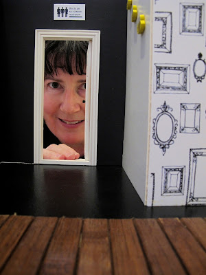 Woman peering through the door to the toilet in a modern dolls' house miniature cafe.