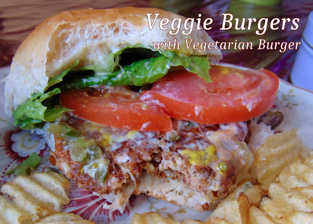 A Veggie Burger with Vegetarian Burger in a bun with lettuce, tomato and condiments, served with potato chips.