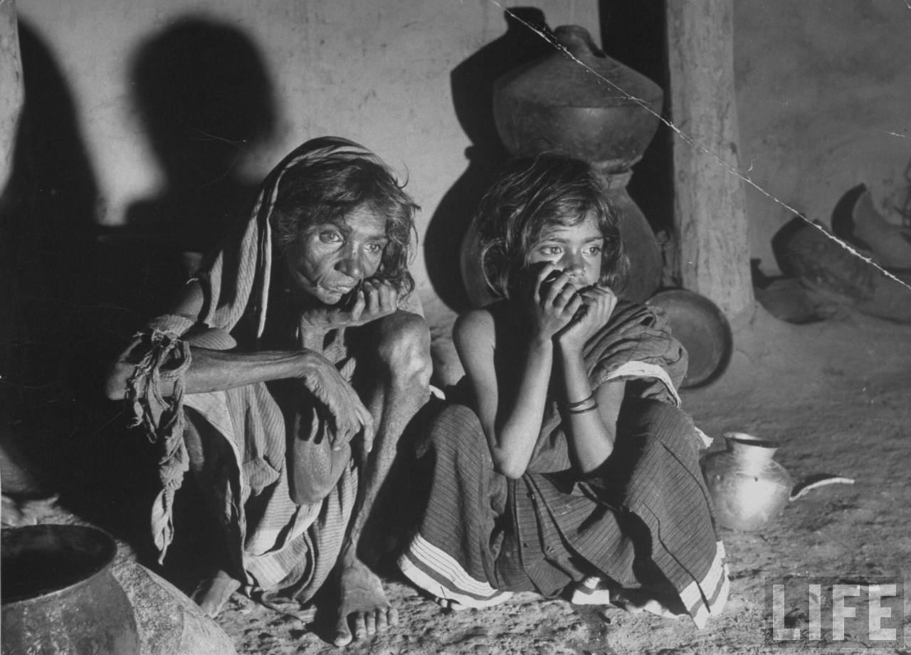 Starving Indian Peasant woman with her young Granddaughter, after cooking a pot of Horse Meat which is the Best they can do during Famine Crisis - 1946