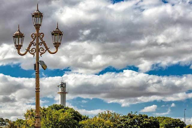 Un conjunto de tres faroles bajo una imponente nube blanca en el cielo.