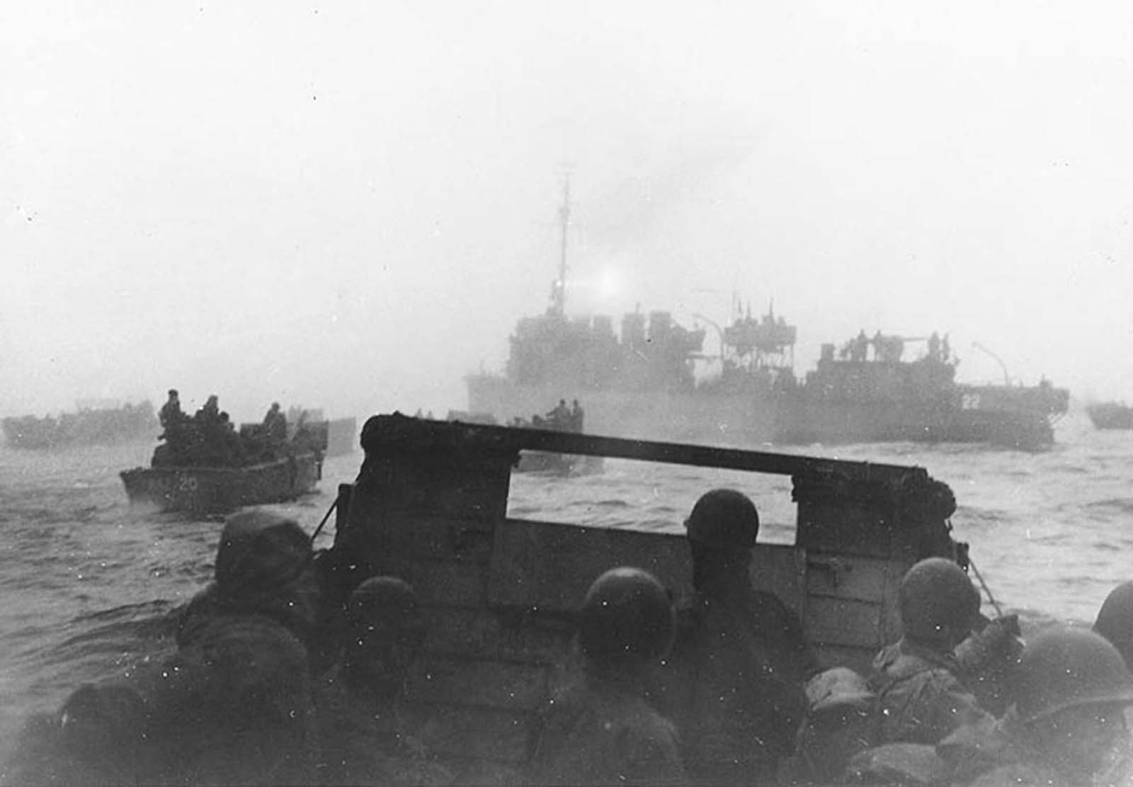 USS Pruitt leads landing craft from USS Heywood toward their landing beaches in Massacre Bay, Attu, on the first day of the May 11, 1943 invasion of Attu. Pruitt used her radar and searchlight to guide the boats nine miles through the fog. The searchlight beam is faintly visible pointing aft from atop her pilothouse. Some 15,000 American and Canadian troops successfully landed on the island.