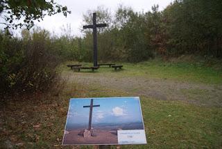 Im Vordergrund: Eine Tafel von RWE, die das Gipfelkreuz an der Abbruchkante zeigt. Im Hintergrund: Das Gipfelkreuz heute. Von einer Abbruchkante ist nichts mehr zu sehen,