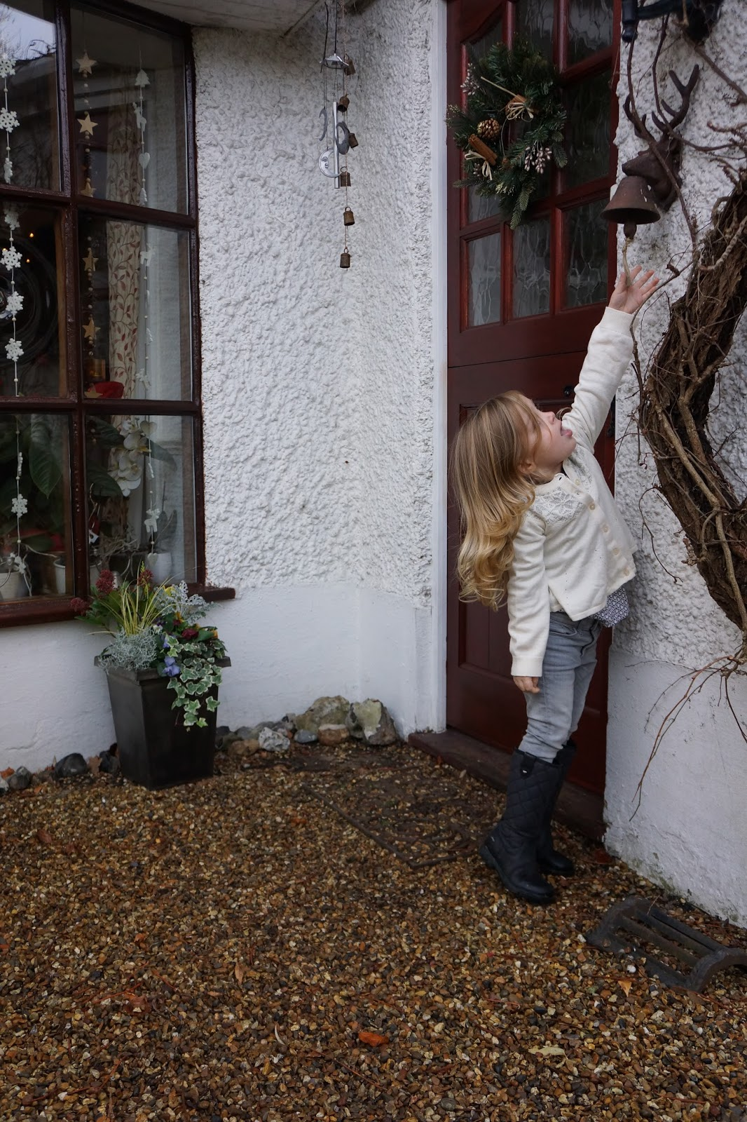 young girl trying to ring a door bell