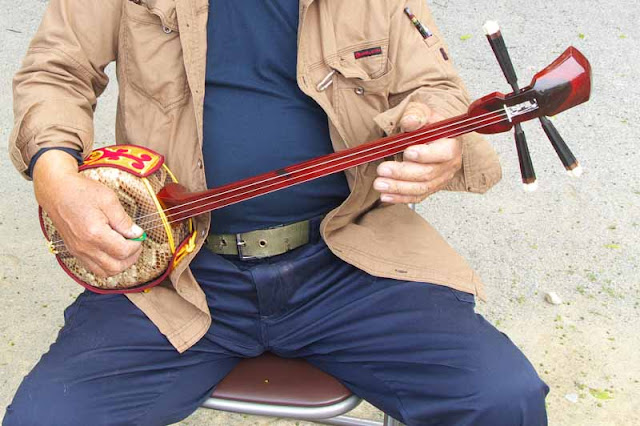 man strumming sanshin, 3-stringed instrument