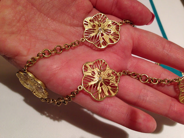 Long gold and diamond flower necklace by Naomi Blumenthal.