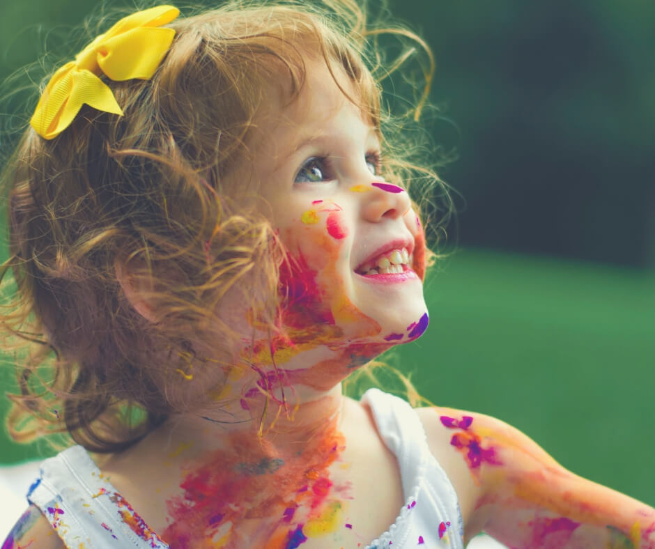 10 Things You'll Learn From Being A Parent | A young girl with her face covered in paint splotches.