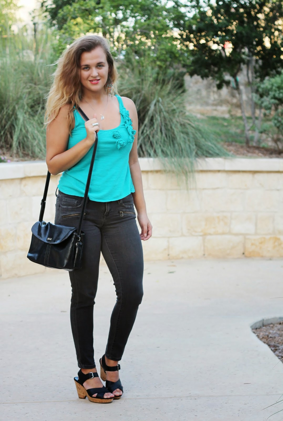 fashion blogger wearing light blue top and skinny jeans