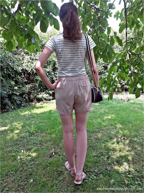 Bluzka w paski, różowe spodenki, beżowe sandały, biało-czarna torebka w kształcie aparatu