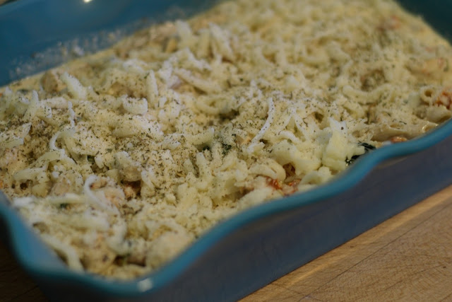 The Cheese added to the top of the Easy Tuscan Chicken Pasta in the baking dish.