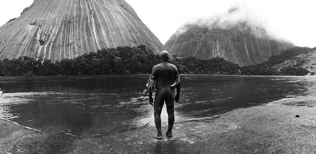 der cineast Filmblog Schamane Karamakate steht am Flussufer und blickt auf Berge