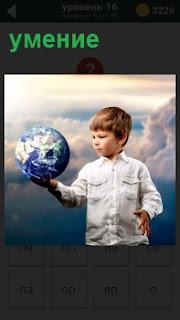 Мальчик умеет держать на одной руке модель земного шарика на фоне облаков