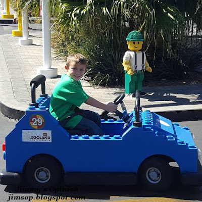 Our grandson Benjamin driving a blue car appearing to be made of lego bricks