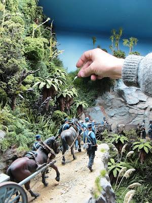 Man straightening a piece of miniature toetoe grass in a diorama bush scene.