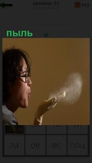 женщина в очках сдувает пыль на своих руках