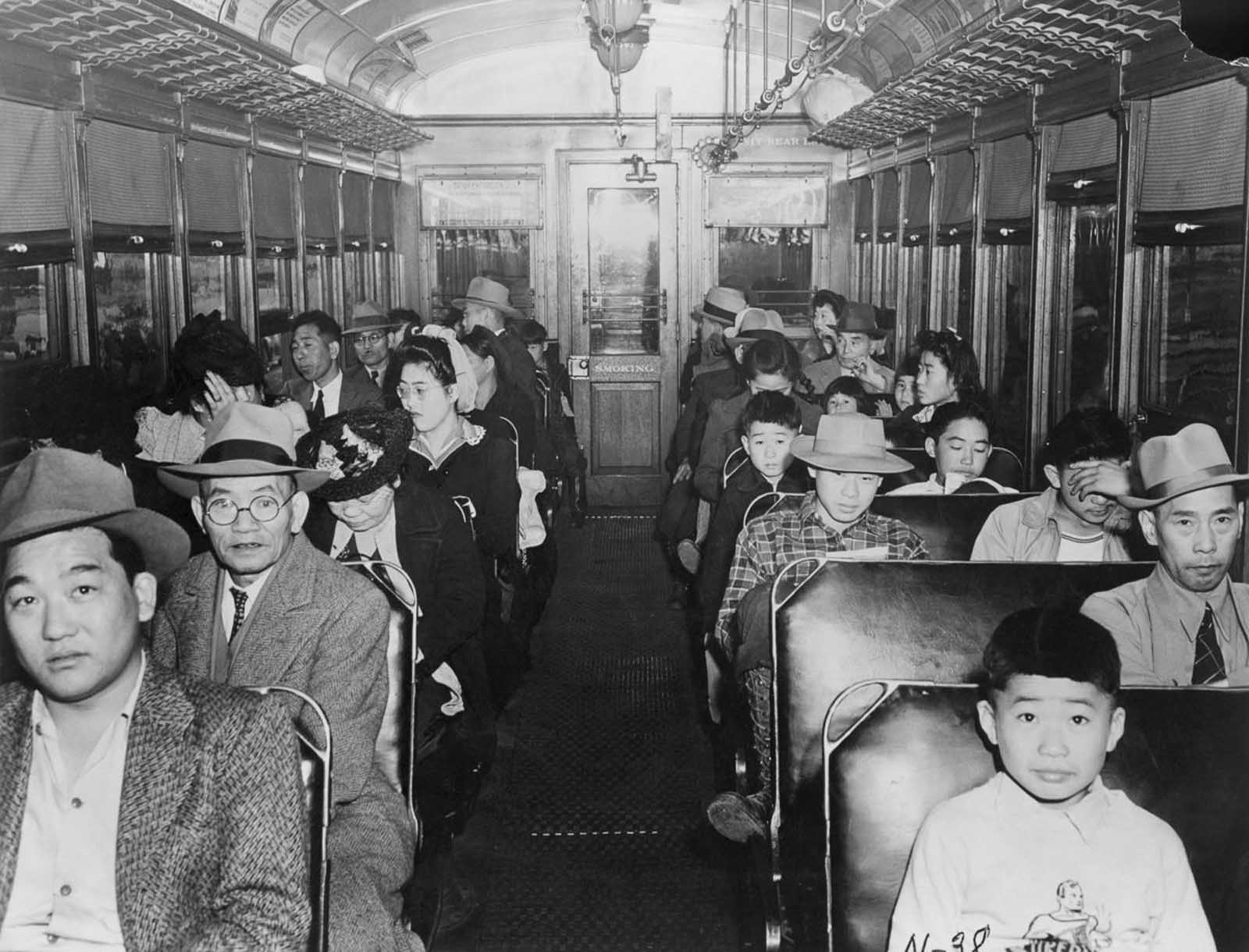 Japanese-Americans ride on a train to an assembly center.