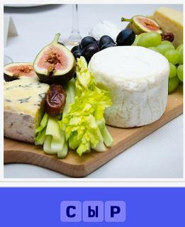 на разделочной доске лежит круг сыра с овощами