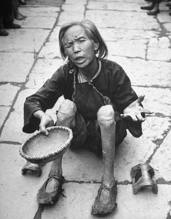 Mulher famélica pede comida nuna imagem rotineira da China revolucionária