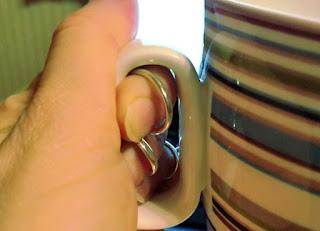 Kuvassa näkyy, kuinka sormituet sormissa voi pitää kahvikupista kiinni.