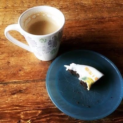 Morgan's Milieu | Baker Days Letterbox Cake Review: A cup of coffee and a piece of cake on a blue plate.