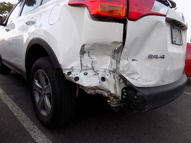 Close up of damage to quarter panel, tailgate and bumper before repairs at Almost Everything Auto Body.
