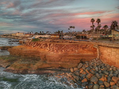 view from water toward land of Tim doing a handstand at Sunset Cliffs