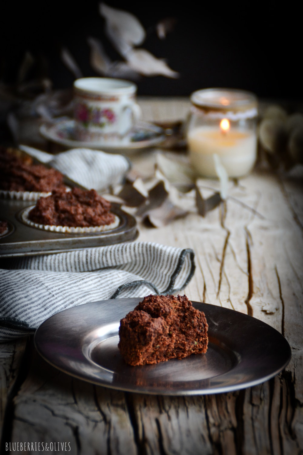 Cocoa muffins in old retro metallic pan, over old wood table, dark background, dry eucalyptus leaves, linen grey kitchen cloth
