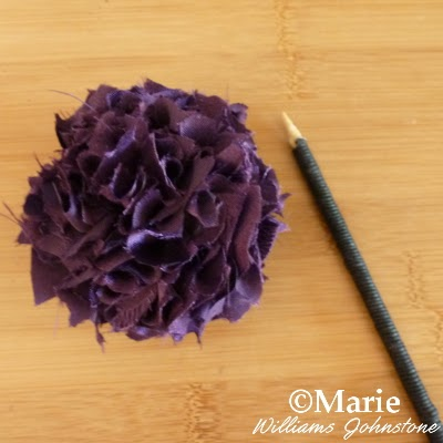 Purple satin fabric pom pom and a black cord wrapped stick