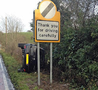 crashed car in ditch with safety sign fail