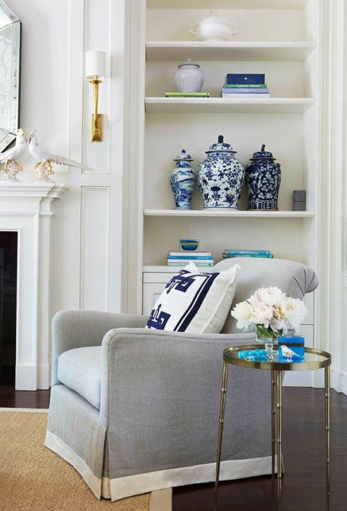 white living room with grey armchair and blue accents