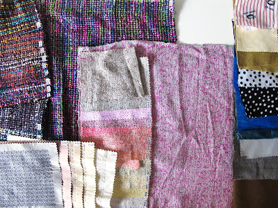 Selection of fabric samples and pieces of fabric, laid out on a table.