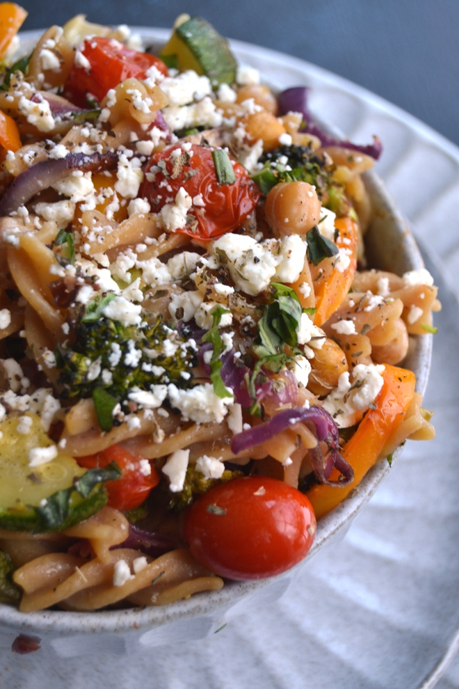 Greek Roasted Vegetable and Chickpea Pasta is made with roasted chickpeas, feta cheese, loads of roasted veggies and an easy lemon vinaigrette for a delicious meal! www.nutritionistreviews.com