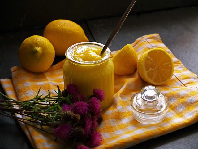 Lemon curd jar decorated with lemons and purple flowers.