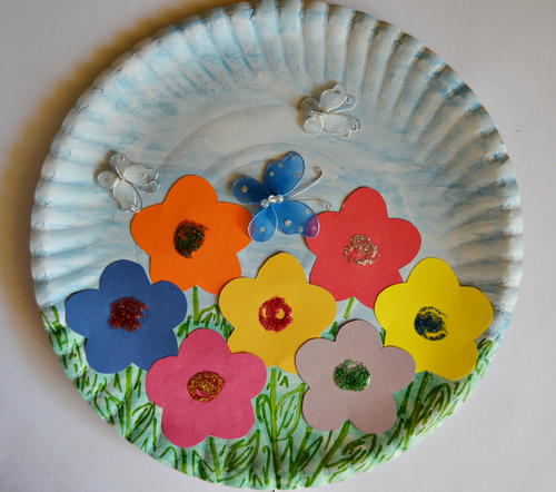 Paper plate munchkins and mayhem a paper plate is colored with a blue sky and green grass and decorated with many colors of cut out paper flowers to make a pretty garden picture mightylinksfo