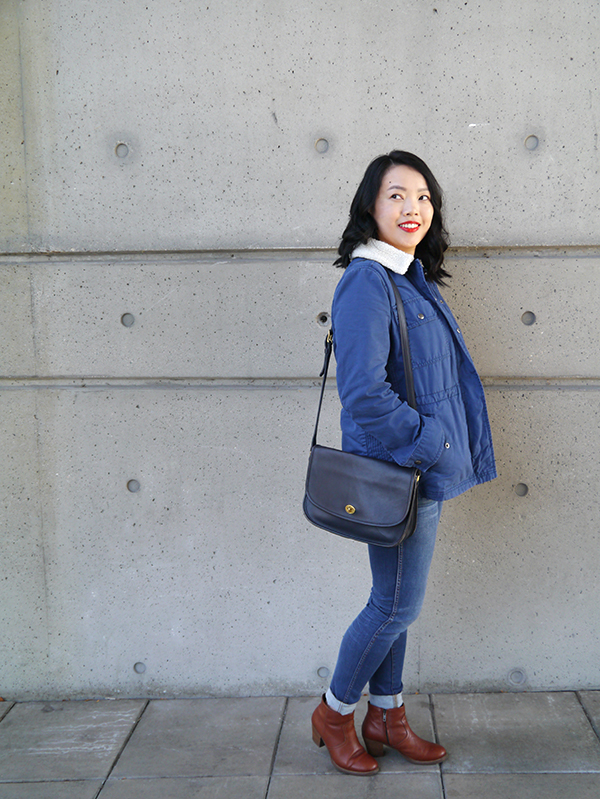Vancouver beauty, life, and style blogger Solo Lisa wears a blue sherpa-lined utility jacket with a fuzzy shearling collar, navy and white striped tee, blue skinny jeans, cognac leather ankle boots, red lipstick, and a vintage bag.