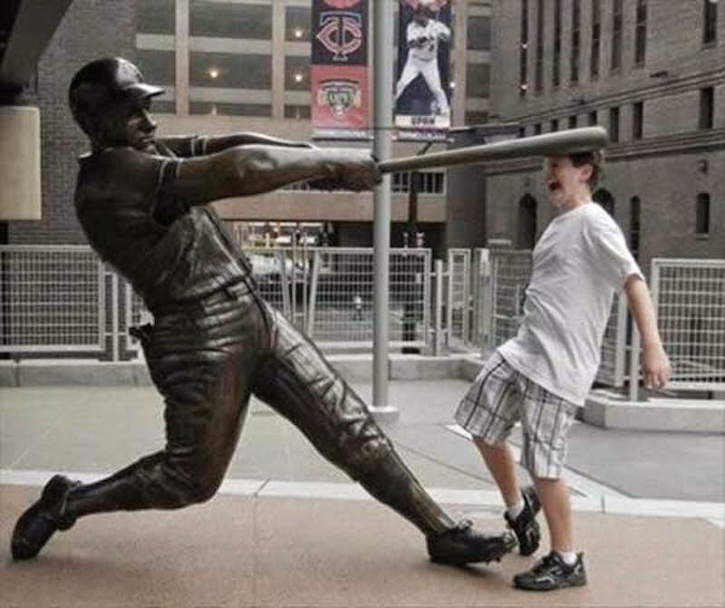 7. Swing batter, batter–judging by the look on this kid's face he really did knock his head on the batt.  - 23 Times Pedestrians Messed With Statues...And It Was Downright Hilarious