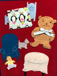 flannel bed with blanket, giant teddy bear, chair, table with cover, dog, and baby