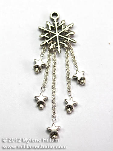 Silver stars dangle daintily from the end of fine jewelry chain attached to a snowflake charm