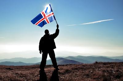 Hombre ondeando la bandera de Islandia a contra luz