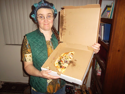 Cynthia Parkhill holds open pizza box tilted toward viewer. Inside, occupying less than half of surface space, are three small slices of pizza